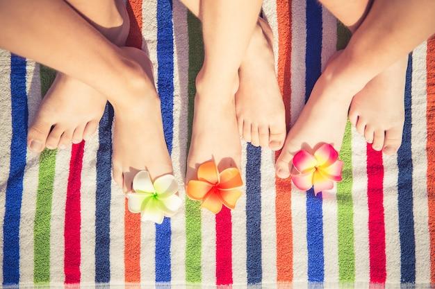Dziecięce stopy z kwiatami na kolorowym tle ręcznika plażowego w paski
