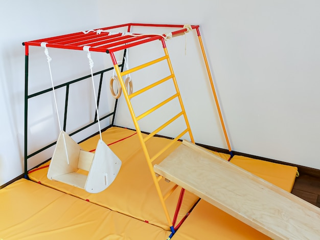 Dziecięcy kompleks sportowy dla malucha w mieszkaniu huśtawka drewniana, plac zabaw, zjeżdżalnia i kółka gimnastyczne.