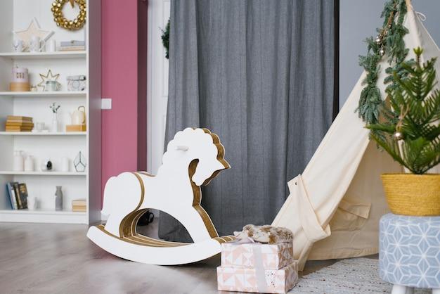 Dziecięcy koń na biegunach wykonany z drewna i kartonu w pokoju dziecięcym, ozdobiony na boże narodzenie i nowy rok