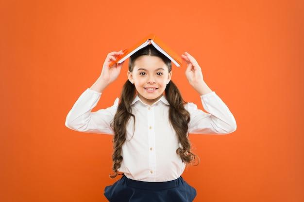 Dziecięcy mundurek szkolny trzyma książkę podekscytowany wiedzą równowaga życiowa i pozytywność