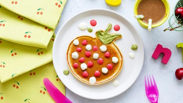 Dziecięcy naleśnik na śniadanie traktuje tło, zabawny kształt truskawki