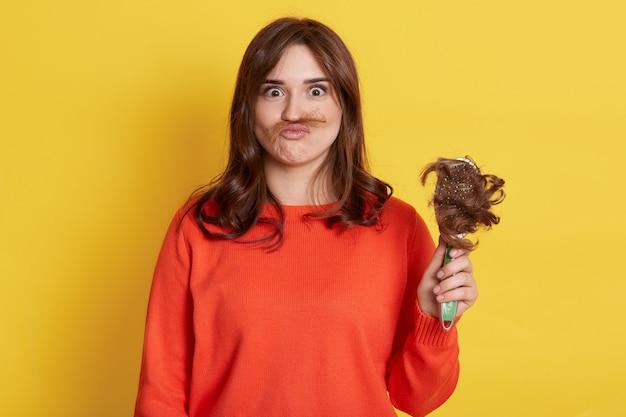 Dziecinna ciemnowłosa kobieta ubrana na co dzień, mająca problem z luźnymi włosami, trzymająca grzebień, robiąc wąsy z włosów, odizolowana na żółtej ścianie.