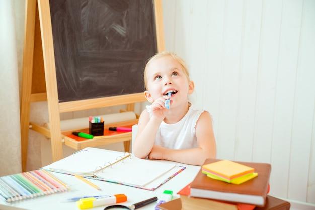 Dzieciństwo i powrót do koncepcji szkoły. dziewczyna z rozważnym wyrazem twarzy robi pracę domową