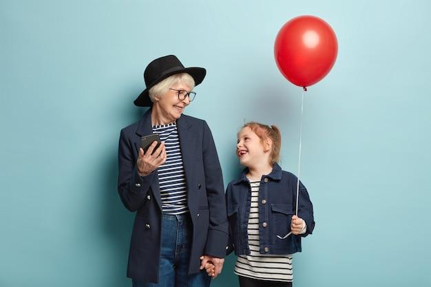 Dzieciństwo, rodzina, koncepcja relacji. stylowa babcia będąca zaawansowanym użytkownikiem nowoczesnych technologii, trzyma za rękę małą wnuczkę