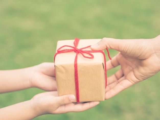 Dziecka i matki ręki z prezenta pudełkiem nad zielonym tłem. zabytkowy styl.