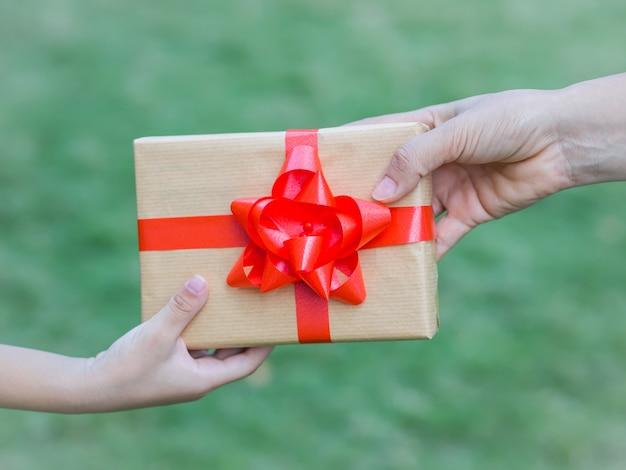 Dziecka i matki ręki z prezenta pudełkiem nad zielonym tłem