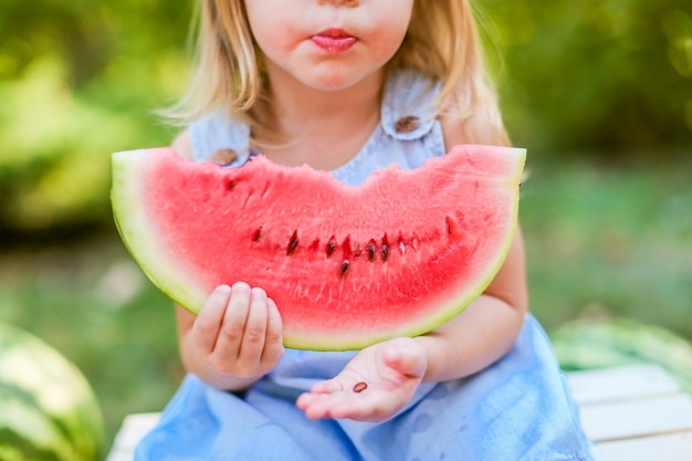 Dziecka łasowania arbuz w ogródzie. dzieci jedzą owoce na zewnątrz. zdrowa przekąska dla dzieci.