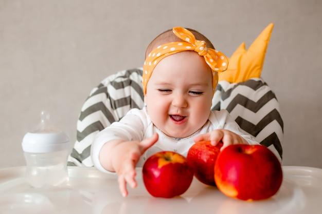 Dziecka łasowania puree owoc siedzi w krzesła zakończeniu up. patrząc na kamery. zdrowy tryb życia. dzieciństwo.