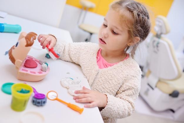 Dziecka mała dziewczynka bawić się w dentystach