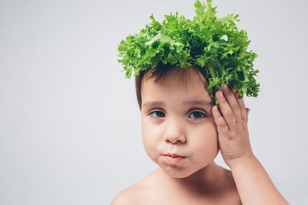 Dziecka mienia sałatek zamknięty up. zabawna czapka z sałatką