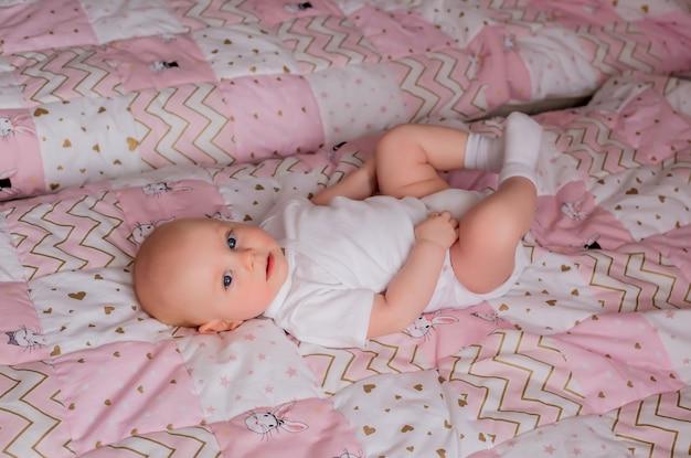 Dziecko 5 miesięcy w białym body leżącym na łóżku z różowym kocem