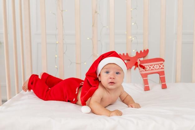Dziecko 6 miesięcy w stroju świętego mikołaja leżące w domowym łóżeczku na brzuchu