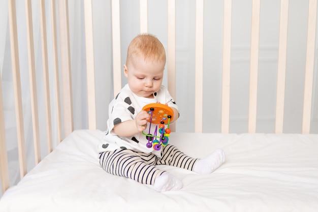 Dziecko 8 miesięcy bawiące się w łóżeczku, wczesny rozwój dzieci do roku, miejsce na tekst