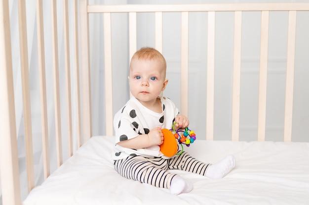 Dziecko 8 miesięcy bawiące się w łóżeczku, wczesny rozwój dzieci do roku