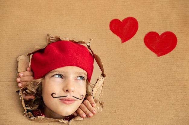 Dziecko artysty trzymające transparent puste szczęśliwe dziecko udaje, że jest malarzem koncepcja walentynek