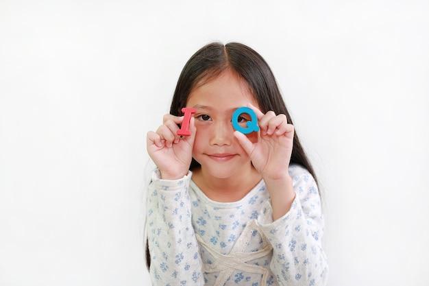Dziecko azjatyckie dziewczynka patrząc przez tekst gąbki iq (iloraz inteligencji) w rękach na białym tle. koncepcja edukacji i rozwoju