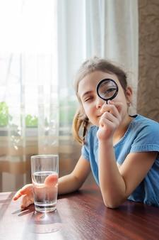 Dziecko bada wodę lupą w szklance