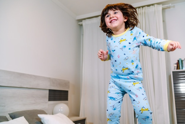 Dziecko bardzo szczęśliwe skacząc na łóżku w piżamie przed pójściem spać