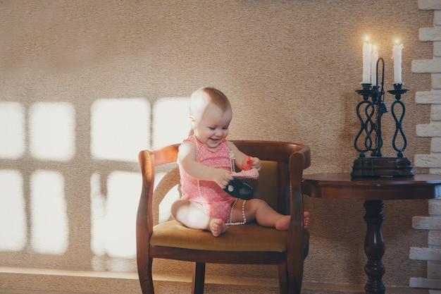 Dziecko bawi się butami. dziewczyna staje się małą damą. koncepcja rozwoju umiejętności motorycznych, gry edukacyjne, dzieciństwo, dzień dziecka, przedszkole. reklamy obuwia i mody. kopia przestrzeń