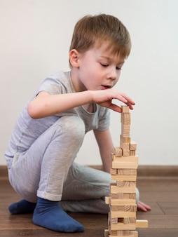 Dziecko bawi się drewnianą wieżą na podłodze