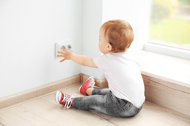 Dziecko bawi się gniazdkiem elektrycznym na podłodze w domu