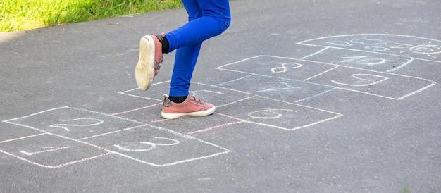 Dziecko bawi się klasykami na placu zabaw na świeżym powietrzu