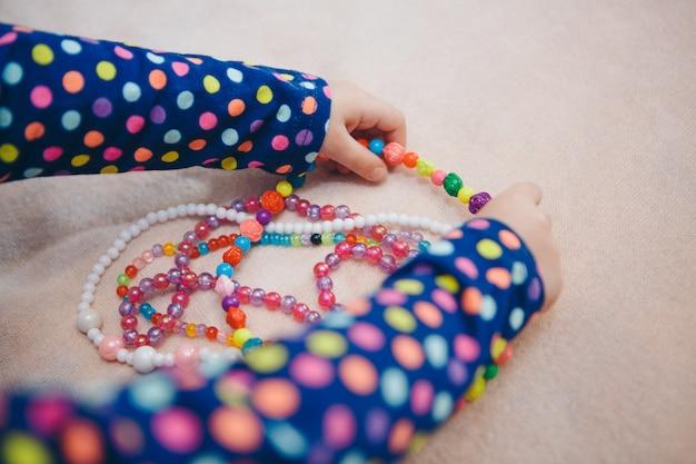 Dziecko bawi się kolorowymi koralikami. dziewczynka staje się małą damą. koncepcja rozwoju umiejętności motorycznych, gry edukacyjne, dzieciństwo, dzień dziecka, przedszkole. biżuteria i moda na kostiumy. copyspace