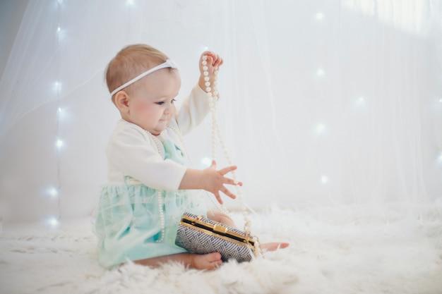Dziecko bawi się kolorowymi koralikami. dziewczynka staje się małą damą. koncepcja rozwoju umiejętności motorycznych, gry edukacyjne, dzieciństwo, dzień dziecka, przedszkole. reklamy biżuterii i mody kostiumowej.