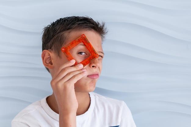 Dziecko bawi się magnetycznym konstruktorem chłopiec bawi się kolorowymi klockami chłopiec przykłada szczegóły konstruktora do twarzy jak okulary