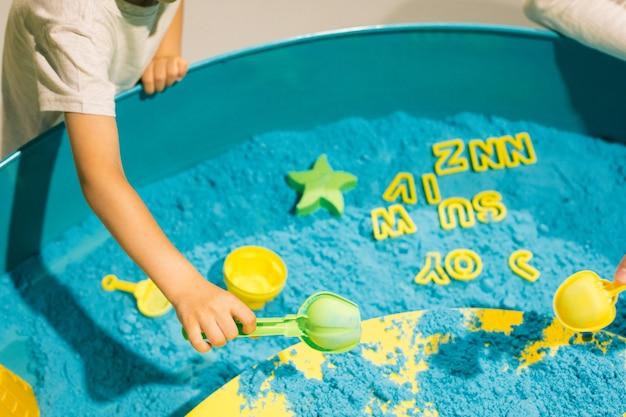 Dziecko bawi się piaskiem kinetycznym. terapia sztuką. łagodzenie stresu i napięcia. wrażenia dotykowe. kreatywność i przyjemność. rozwój umiejętności motorycznych. koncentracja i uwaga.