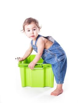 Dziecko bawi się plastikowym pojemnikiem na białym tle