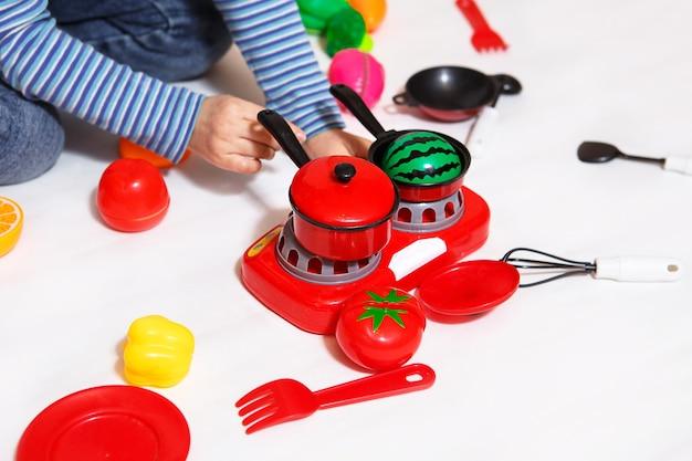Dziecko bawi się plastrowanymi plastikowymi warzywami i owocami na rzepy, gotuje jedzenie na zabawkowej kuchence w misce. gotowanie dla dzieci, dziewczyna uczy się gotować. białe tło, zbliżenie, koncepcja.