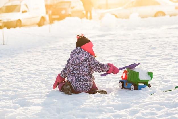 Dziecko bawi się samochodem i łopatą. koncepcja odśnieżania miasta