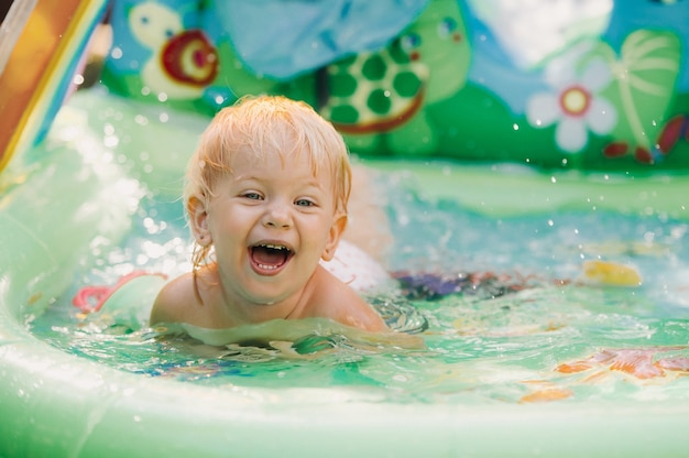 Dziecko bawi się w basenie. mała dziewczynka w basenie, uśmiechnięte dziecko.