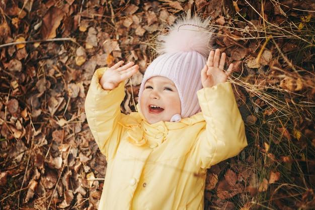 Dziecko bawi się w lesie. park jesień. koncepcja mody, akcesoriów, spacerów na świeżym powietrzu