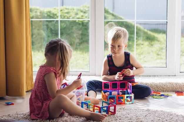 Dziecko bawi się wielokolorowym magnetycznym konstruktorem, budując wieżę. zabawki edukacyjne dla małych dzieci. element konstrukcyjny dla niemowlaka lub małego dziecka bałagan w pokoju zabaw