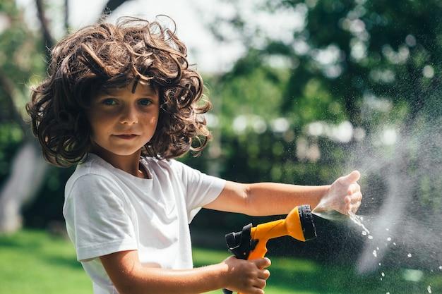 Dziecko bawi się wodą na podwórku w ogrodzie