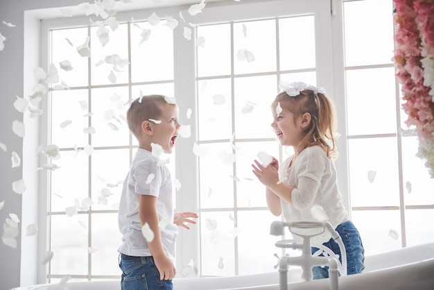 Dziecko bawi się z ikry płatki w domowej łazience. mała dziewczynka i chłopiec fawing zabawy i radości razem. dzieciństwo i realizacja marzeń, fantazji, wyobraźni