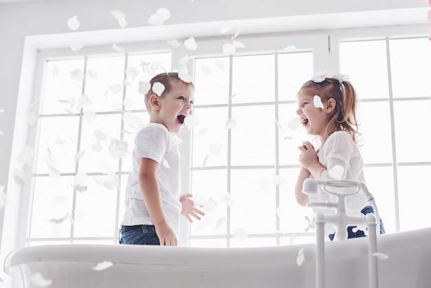 Dziecko bawi się z płatków róży w domowej łazience. mała dziewczynka i chłopiec fawing zabawy i radości razem. dzieciństwo i realizacja marzeń, fantazji, wyobraźni
