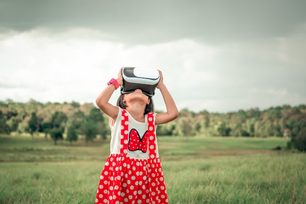 Dziecko bawi się zabawnymi okularami rzeczywistości wizualnej lub technologią vr na pięknej łące
