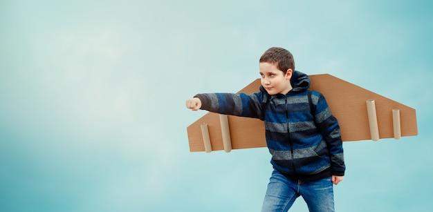 Dziecko bawi się ze skrzydłami samolotu. wolność marzeń. szczęśliwe dzieciństwo