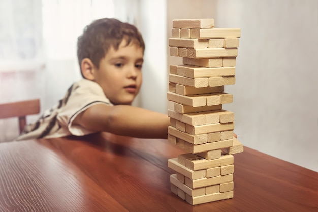 Dziecko bawiące się drewnianymi klockami układa grę, koncepcję uczenia się i rozwoju w tle