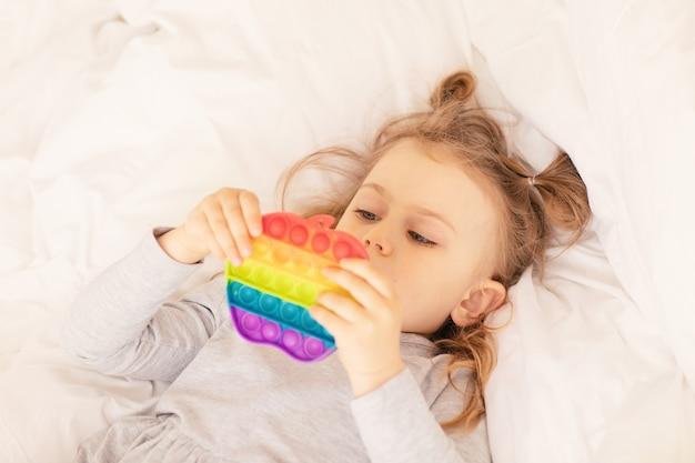 Dziecko bawiące się i relaksujące z pastelowym pop it fidget leżącym na białym łóżku popularna elastyczna zabawka sensoryczna dla dzieci rozwija zdolności motoryczne antystresowa zabawka popit prosty dołek