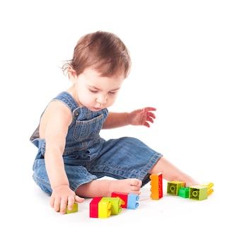 Dziecko bawiące się kolorowymi klockami na białym tle