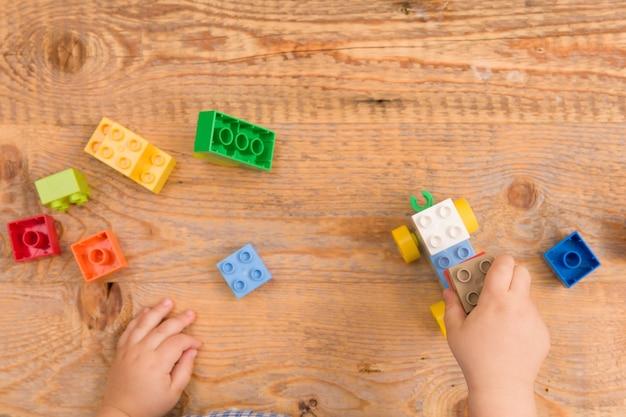 Dziecko bawiące się kolorowymi klockami zabawkowymi na drewnianym tle