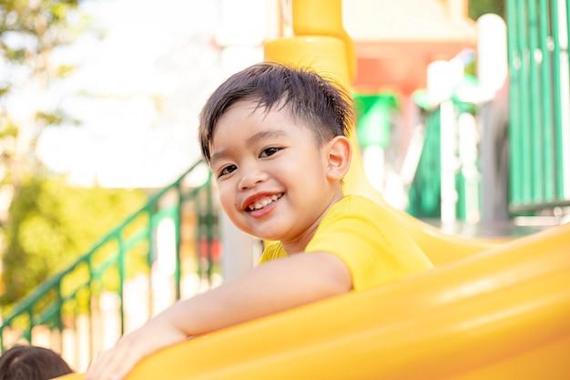 Dziecko bawiące się na placu zabaw na świeżym powietrzu. dzieci bawią się na podwórku szkoły lub przedszkola. aktywny dzieciak na kolorowej zjeżdżalni i huśtawce. zdrowa letnia aktywność dla dzieci.