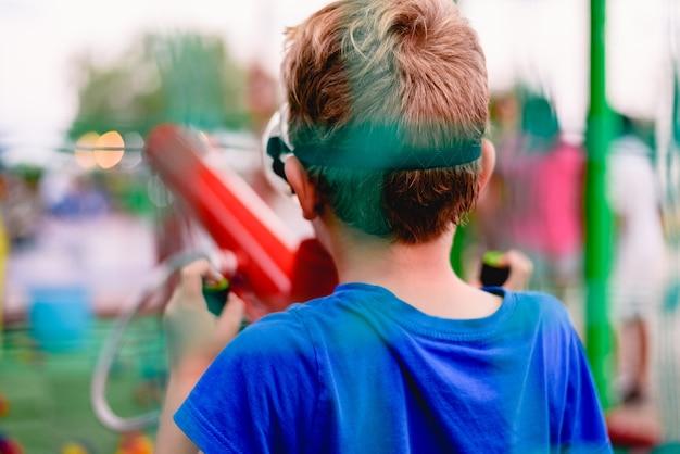Dziecko bawiące się na targach letnich z armatą kolorowych kulek sprężonego powietrza.