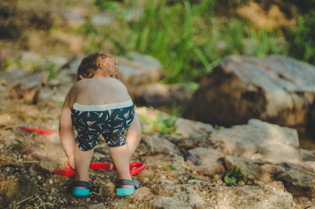 Dziecko bawiące się na zewnątrz. dzieciaku wsypujemy piasek do czerwonej ciężarówki. gry uliczne dla dzieci. chłopiec bawi się maszyną na dużym dzienniku