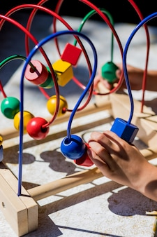 Dziecko bawiące się paciorkami w labiryncie zabawek dla dzieci. labirynt drewnianych koralików. dzieci uczą się kolorów, formy i liczenia. doskonalą umiejętności motoryczne.