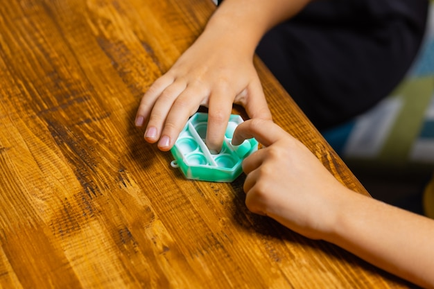 Dziecko bawiące się pop-itwyciskającym bąbelki czubkiem palca.nowa zabawka antystresowa dla dzieci...